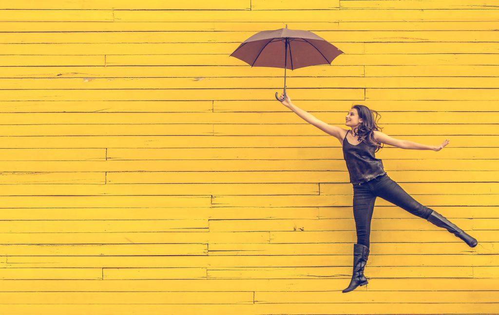 Frau mit Regenschirm vor gelbem Hintergrund